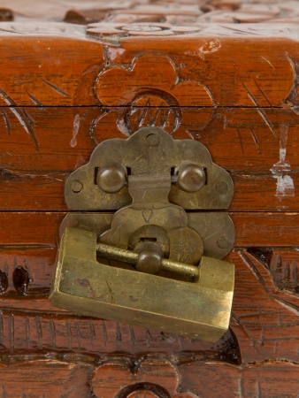 Old padlock on a wooden chest made in Suriname, isolated on white photo