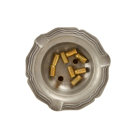 casings: Burning cigarette and empty 9mm bullet casings in an old tin ashtray, isolated Stock Photo