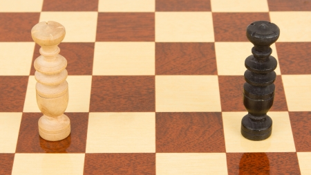 defeated: Two handcarved wooden kings on a chessboard Stock Photo