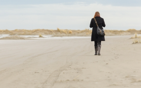 Lonely woman walking on a beach in Holland Stock Photo - 17069072