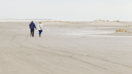 Couple walking on a dutch beach in the winter photo
