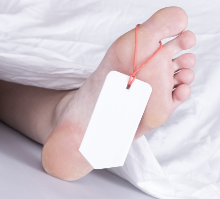 toe tag: Dead body with toe tag, under a white sheet