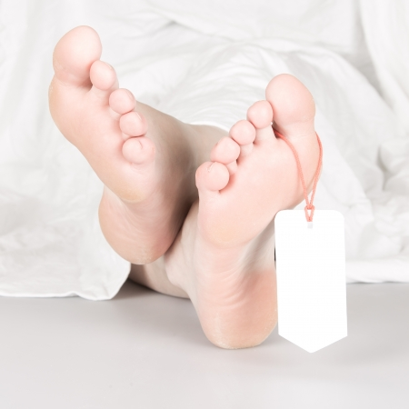 toe tag: Relaxed dead body with toe tag, under a white sheet, relaxed Stock Photo