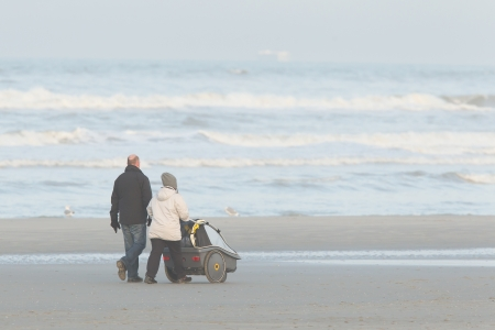 Rear view of a young couple, with the female pushing a pram and walking along a beach photo