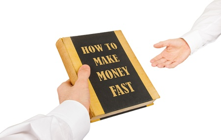 Businessman giving an used book to another businessman, how to make money fast