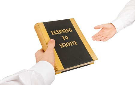 Businessman giving an used book to another businessman, learning to survive Stock Photo