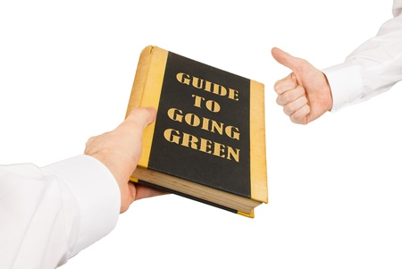 going green: Businessman giving an used book to another businessman, guide to going green Stock Photo