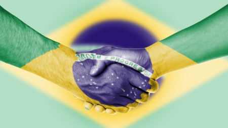Man and woman shaking hands, arms wrapped in the flag of Brazil photo