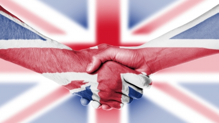 Man and woman shaking hands, arms wrapped in the flag the UK photo