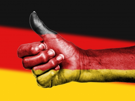German flag on thumbs up hand isolated on a flag background photo