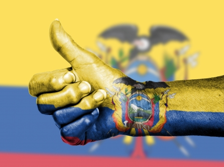Old woman with arthritis giving the thumbs up sign, wrapped in flag pattern, Ecuador photo
