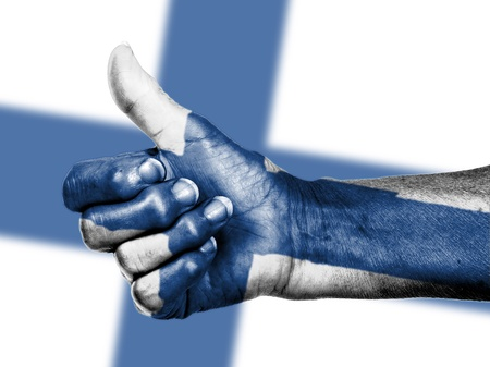 Old woman with arthritis giving the thumbs up sign, wrapped in flag pattern, Finland Stock Photo