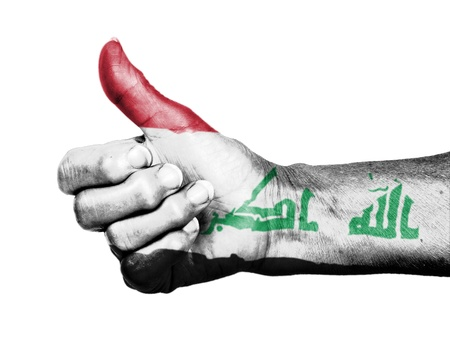 picking up: Old woman with arthritis giving the thumbs up sign, wrapped in flag pattern, Iraq