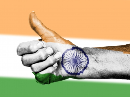 picking up: Old woman with arthritis giving the thumbs up sign, wrapped in flag pattern, India
