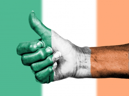 Old woman with arthritis giving the thumbs up sign, wrapped in flag pattern, Ireland photo