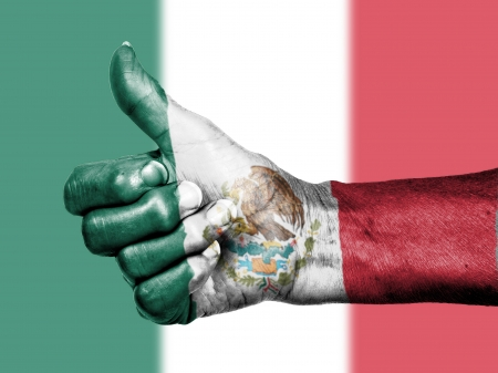 Old woman with arthritis giving the thumbs up sign, wrapped in flag pattern, Mexico photo