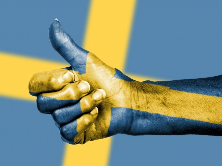 Old woman with arthritis giving the thumbs up sign, wrapped in flag pattern, Sweden photo