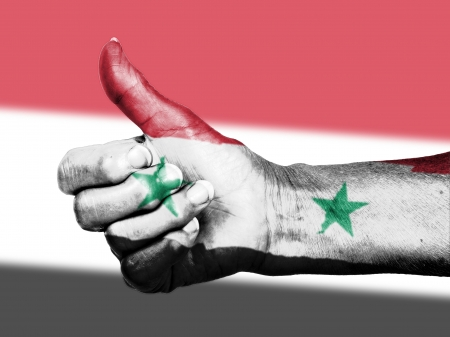 picking up: Old woman with arthritis giving the thumbs up sign, wrapped in flag pattern, Syria Stock Photo