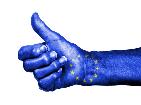 picking up: Old woman with arthritis giving the thumbs up sign, wrapped in flag pattern, European Union Stock Photo