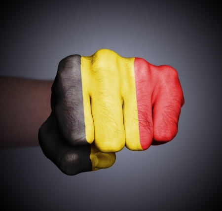 Front view of punching fist on gray background, flag of Belgium