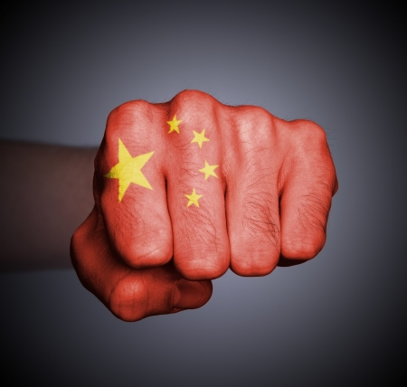 Front view of punching fist on gray background, flag of China
