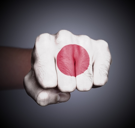 Front view of punching fist on gray background, flag of Japan photo