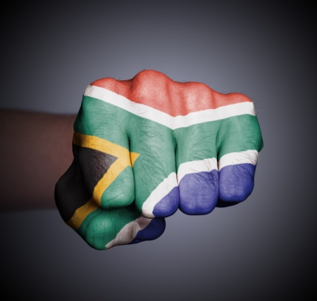 south african flag: Front view of punching fist on gray background, flag of South Africa Stock Photo
