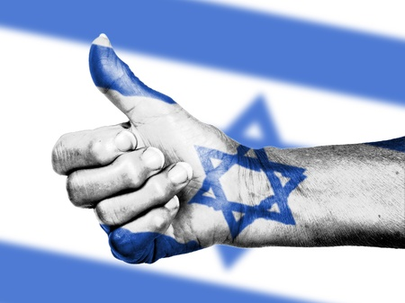 Old woman with arthritis giving the thumbs up sign, wrapped in flag pattern, Israel Stock Photo - 17520219