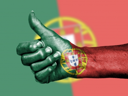Old woman with arthritis giving the thumbs up sign, wrapped in flag pattern, Portugal photo