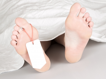 Dead body with toe tag, under a white sheet photo