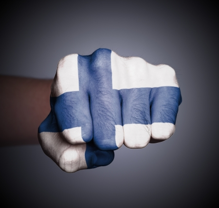 Front view of punching fist on gray background, flag of Finland photo