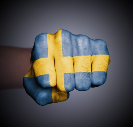 Front view of punching fist on gray background, flag of Sweden photo