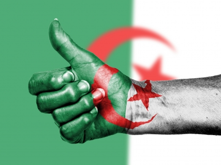 Old woman with arthritis giving the thumbs up sign, wrapped in flag pattern, Algeria photo