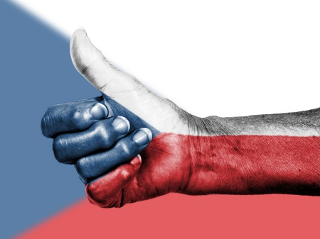 Old woman with arthritis giving the thumbs up sign, wrapped in flag pattern, The Czech Republic Stock Photo - 17733956
