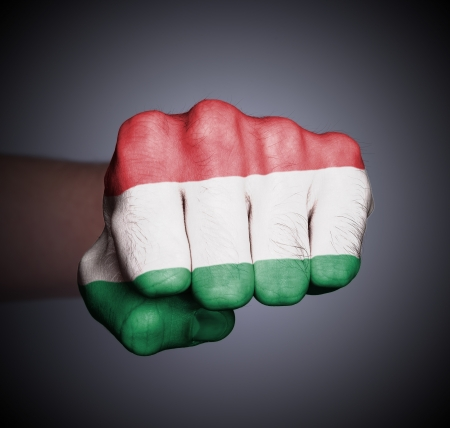 Front view of punching fist on gray background, flag of Hungary