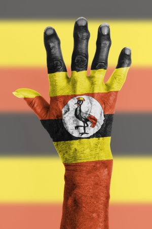 Hand of an old woman wrapped in flag of Uganda photo
