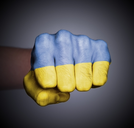 Front view of punching fist on gray background, flag of Ukraine photo