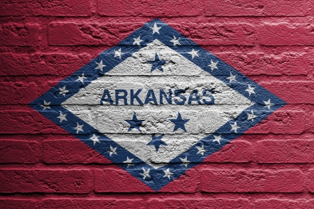brick and mortar: Brick wall with a painting of a flag isolated, Arkansas Stock Photo