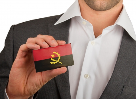 Businessman is holding a business card, flag of Angola Stock Photo - 18031084