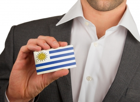 Businessman is holding a business card, flag of Uruguay Stock Photo - 18031080