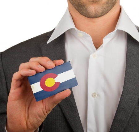 patiotic: Businessman is holding a business card, flag of Colorado Stock Photo