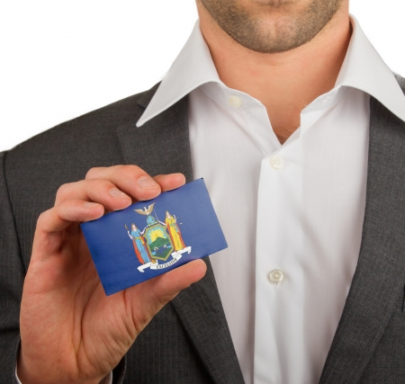 patiotic: Businessman is holding a business card, flag of New York Stock Photo