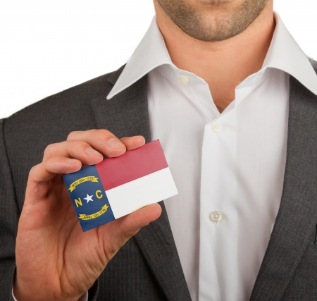 patiotic: Businessman is holding a business card, flag of North Carolina Stock Photo