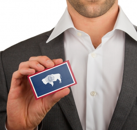 Businessman is holding a business card, flag of Wyoming Stock Photo - 18031081