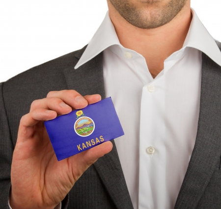 patiotic: Businessman is holding a business card, flag of Kansas Stock Photo