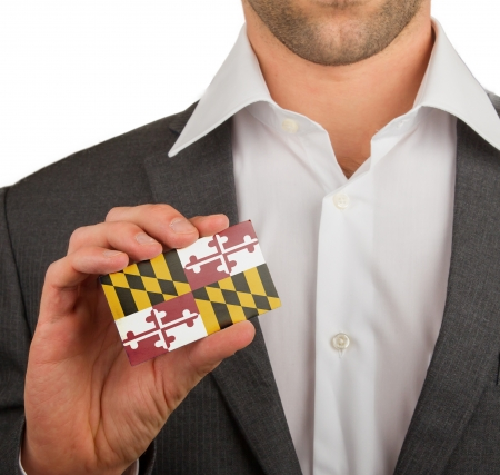 Businessman is holding a business card, flag of Maryland Stock Photo