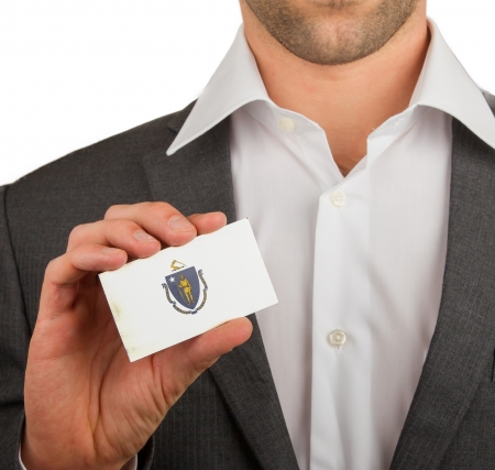 Businessman is holding a business card, flag of Massachusetts Stock Photo - 18050465