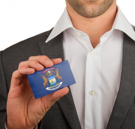 patiotic: Businessman is holding a business card, flag of Michigan Stock Photo