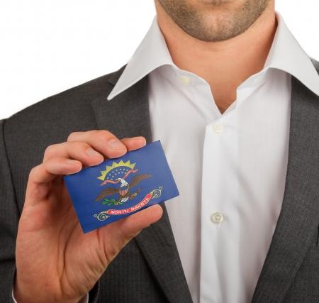 Businessman is holding a business card, flag of North Dakota