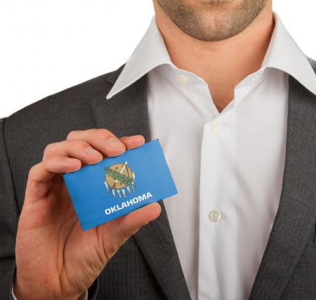patiotic: Businessman is holding a business card, flag of Oklahoma